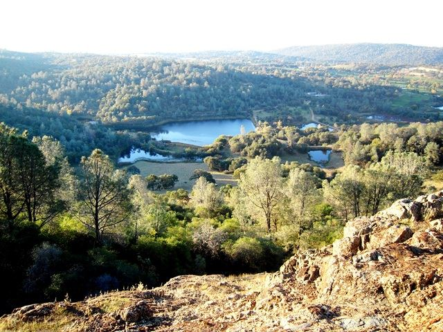 Looking Over a Rocky Ledge into Valley of Trees and Lakes
